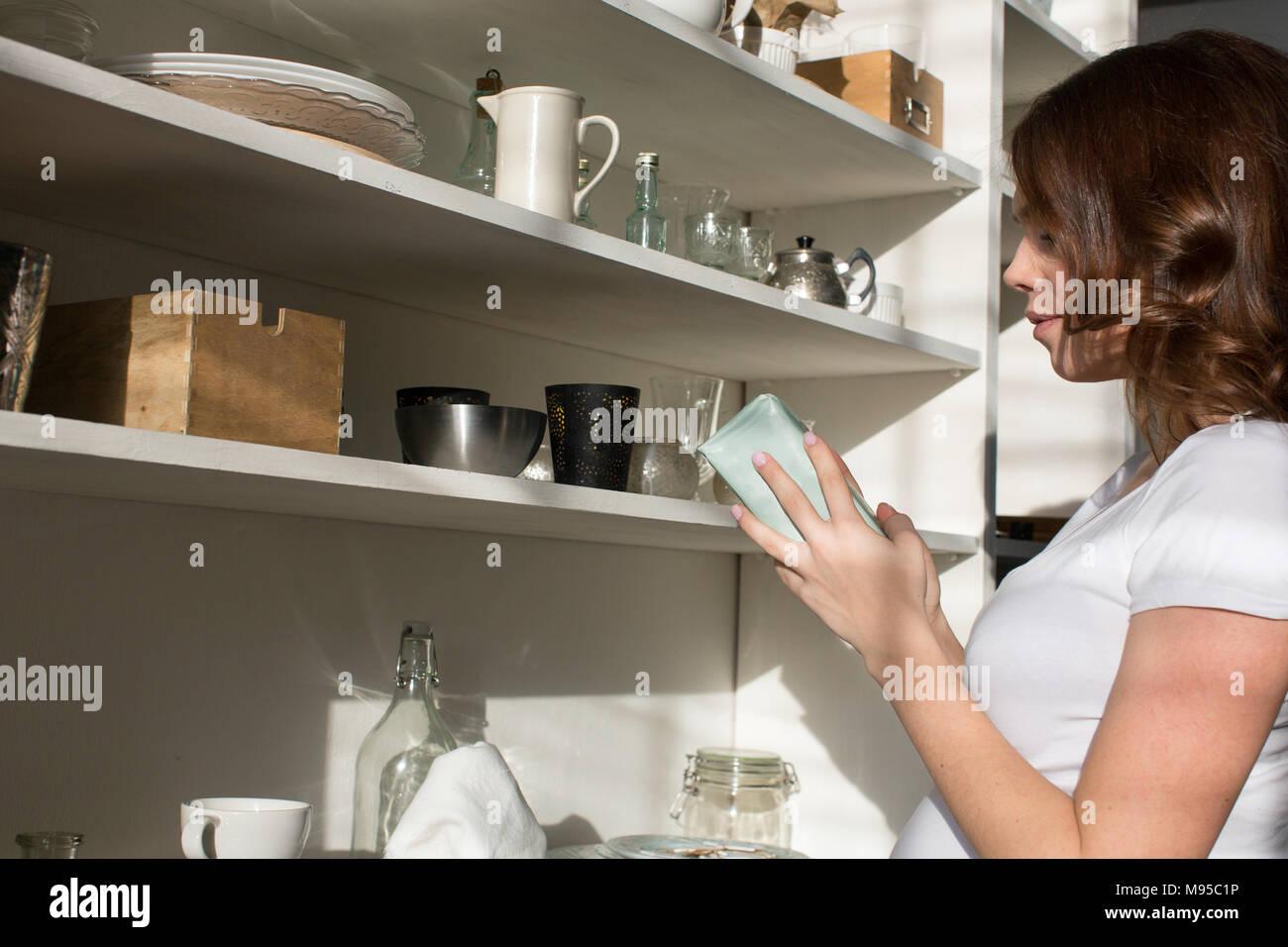 Female taking box from shelf - Stock Image