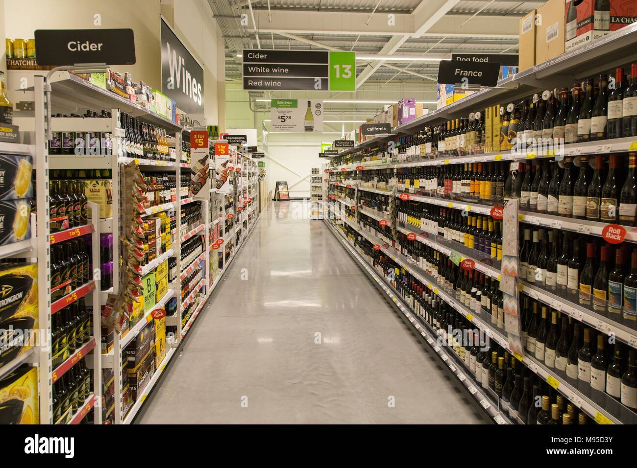 Wine and spirits on full shelves in an Asda supermarket. - Stock Image