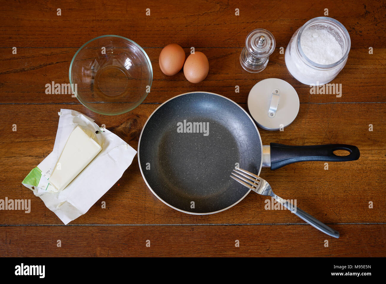 Preparation of fried eggs on a wooden table - Stock Image