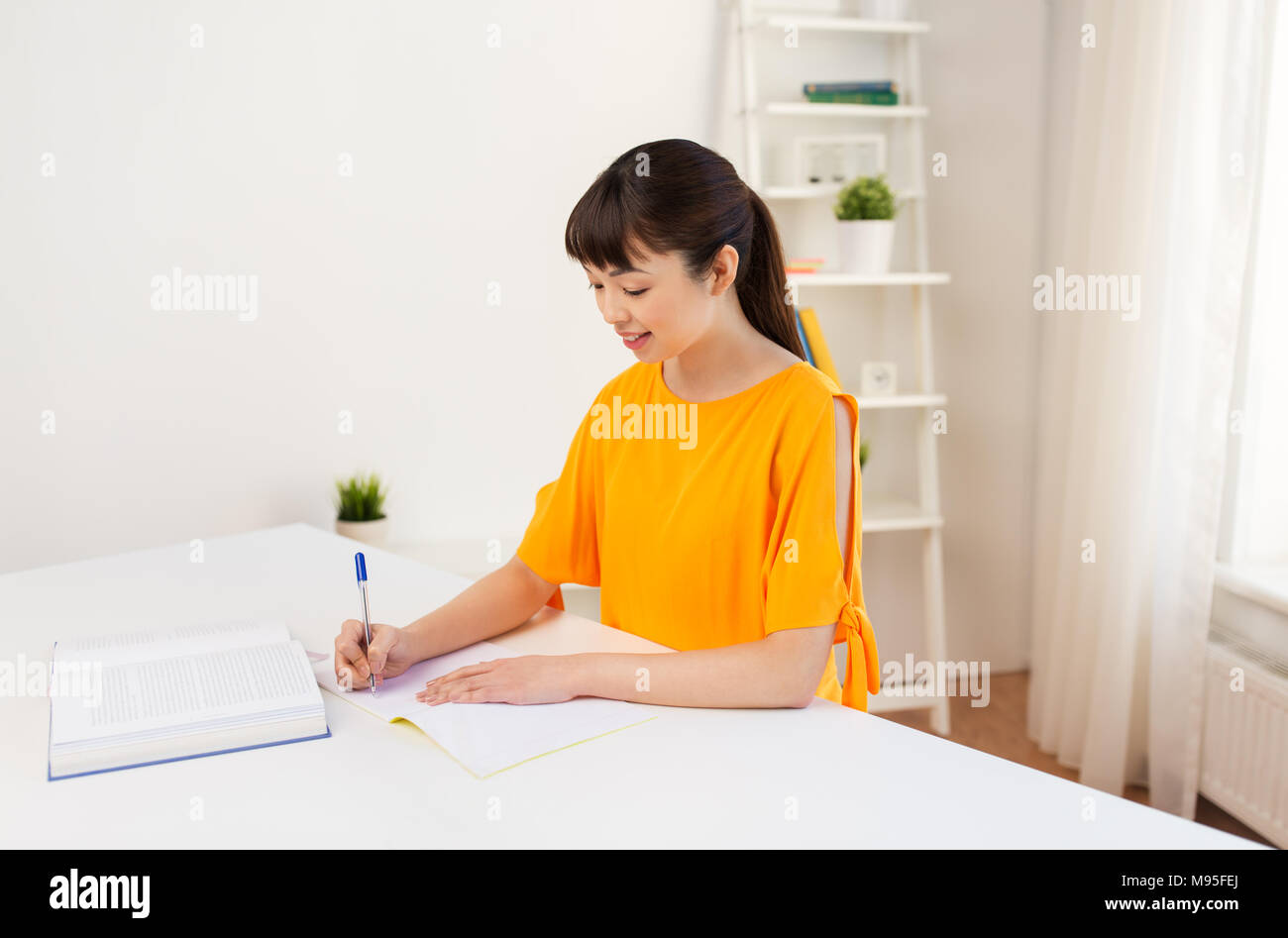 happy student girl with book and notebook at home - Stock Image