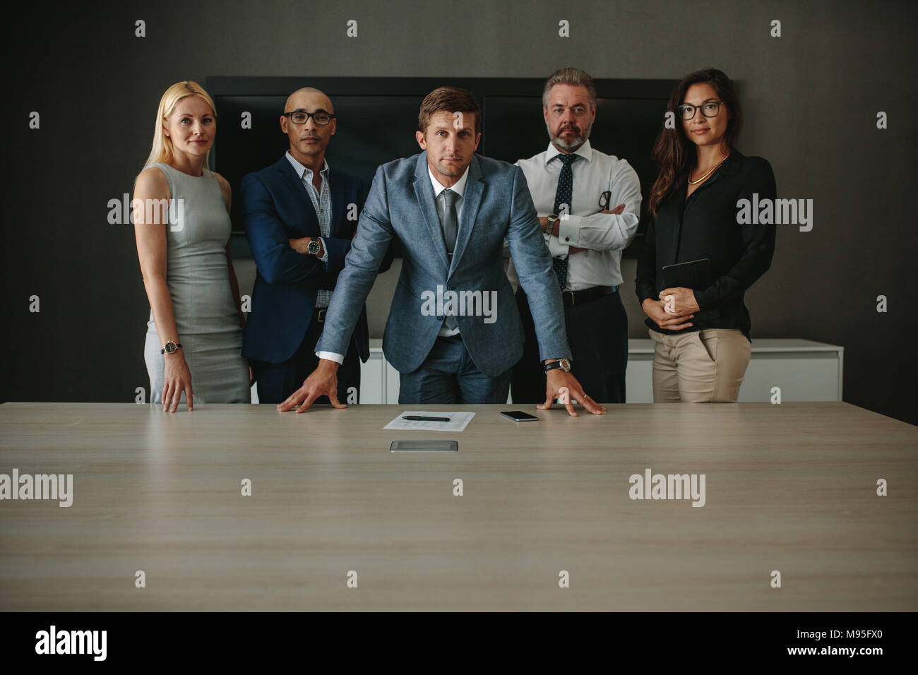 Portrait of confident multi ethnic group of businesspeople looking at camera while standing together at conference table. Corporate professionals in o - Stock Image