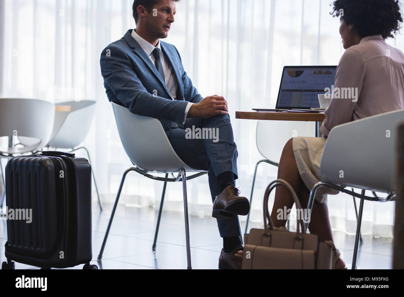 Two business colleagues sitting at airport lounge and discussing work while waiting for their flight. Business travelers talking at airport waiting ar - Stock Image