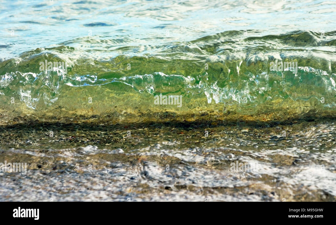 Soft wave rolling onto beach at eye level Stock Photo