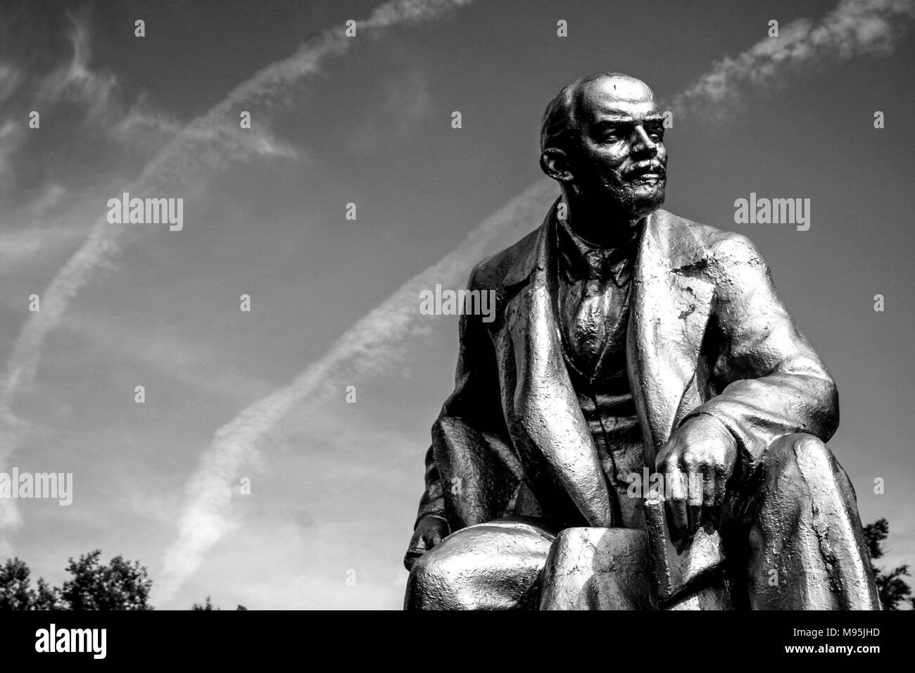 A black and white image of a statue Lenin in a square near St Petersburg, with contrails from aircraft in the sky. Stock Photo