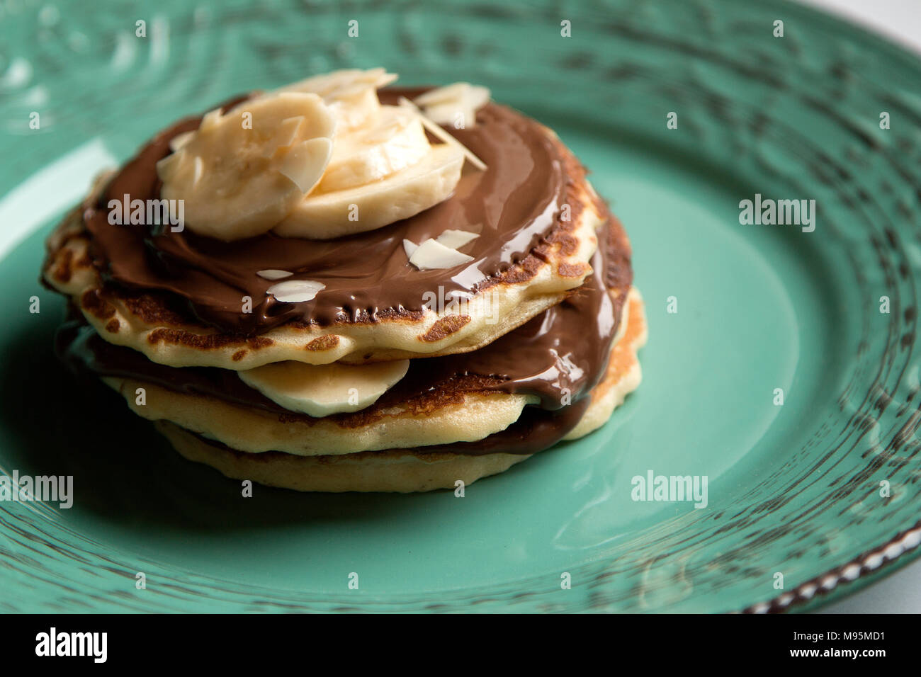 American pancakes with chocolate and banana on a green rustic plate Stock Photo