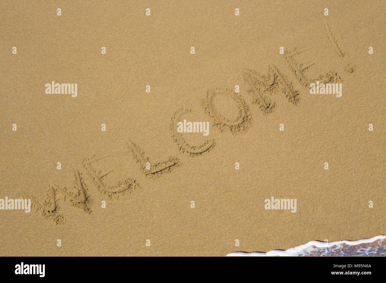 Inscription welcome on a wet sand the writing sea - Stock Image