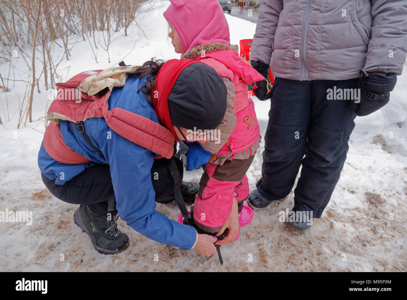 A mother doing up the snowshoes on a little girl (3 yrs old) in Quebec Canada - Stock Image
