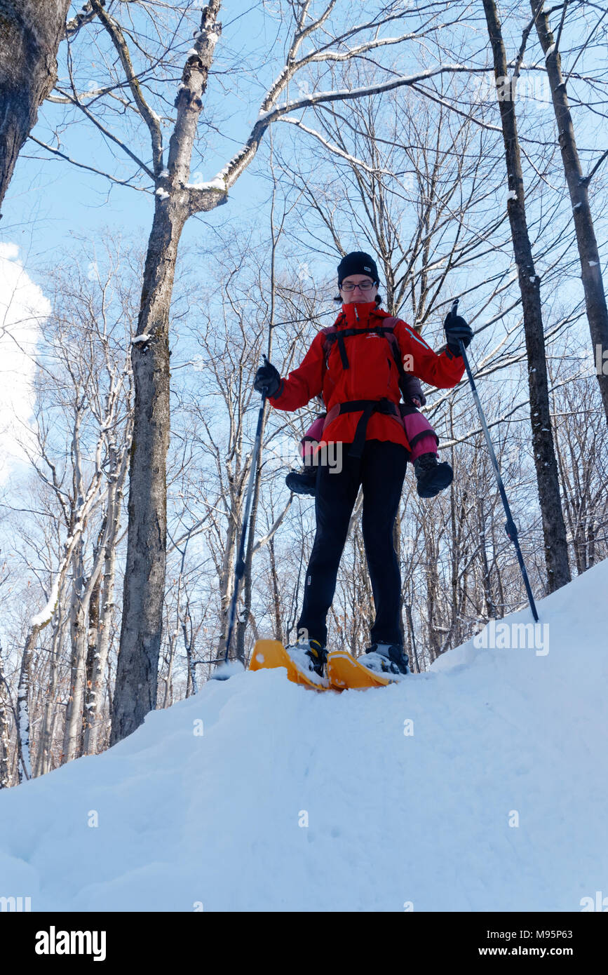 A mother snowshoeing in Quebec Canada with her three year old child on her back Stock Photo