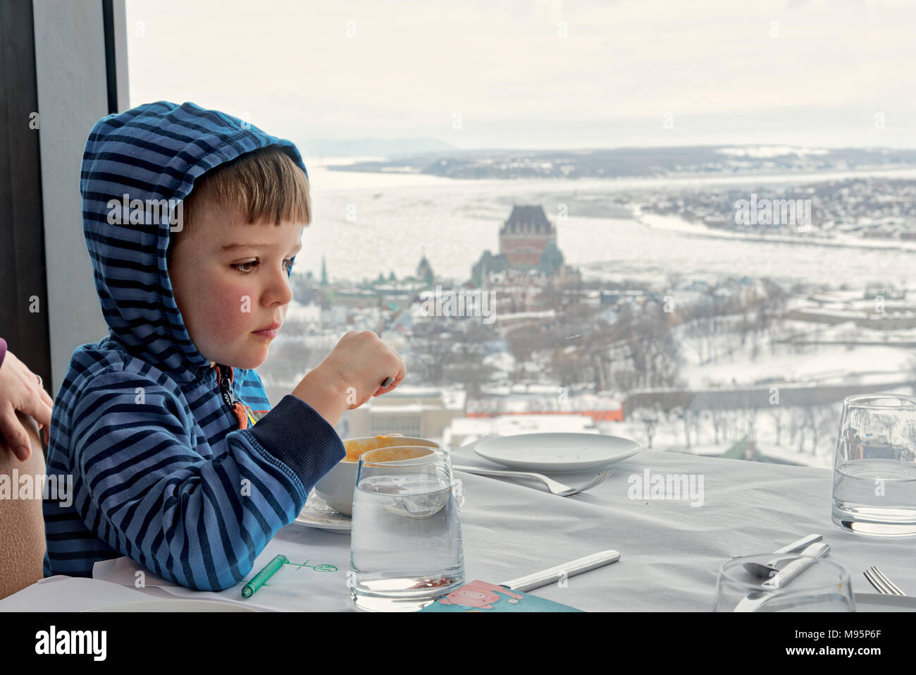 A five year old boy eating in the Ciel! rotating restaurant in Quebec City, with the Chateau Frontenac and the frozen St Lawrence beyond. - Stock Image