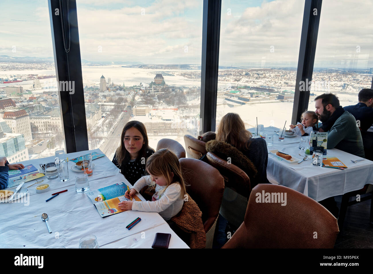 Families dining in the Ciel! rotating restaurant in Quebec City, with iews across the frozen St Lawrence and the Chateau Frontenac - Stock Image
