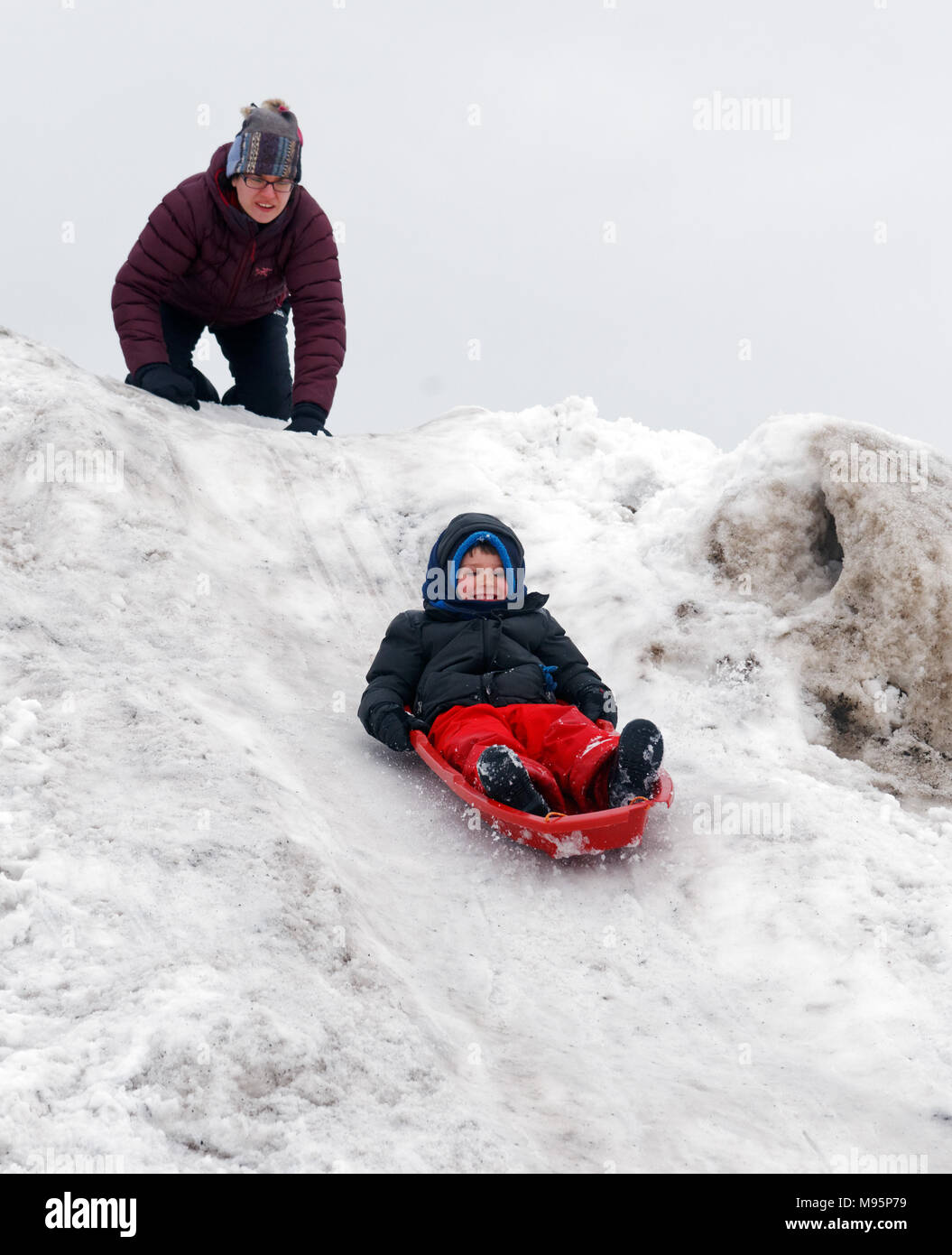 A mum watches anxiously as her son sledges down a very steep icy and wickedly quick slope - Stock Image