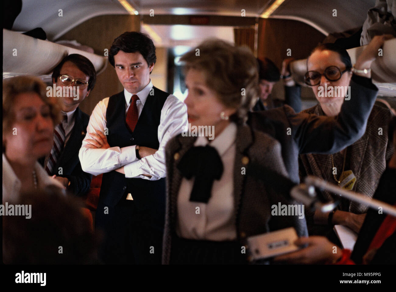 "A White House press staff member looks at First Lady Nancy Reagan as she answers questions from the press on a  White House jet from Florida in February 1982.  This is part of an anit dug campaign , :Just Say No""   Photograph by Dennis Brack - Stock Image"