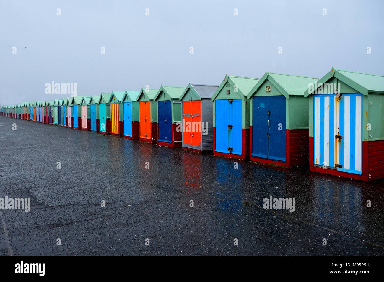 a line of 40 Beach huts with different multicoloured doors on a concrete promenade, the nearest beach huts on the right of the image are large going t - Stock Image