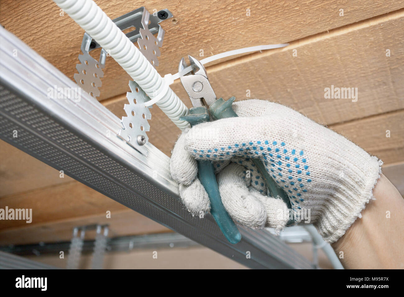 The builder lays the electrical wiring on the ceiling Stock Photo