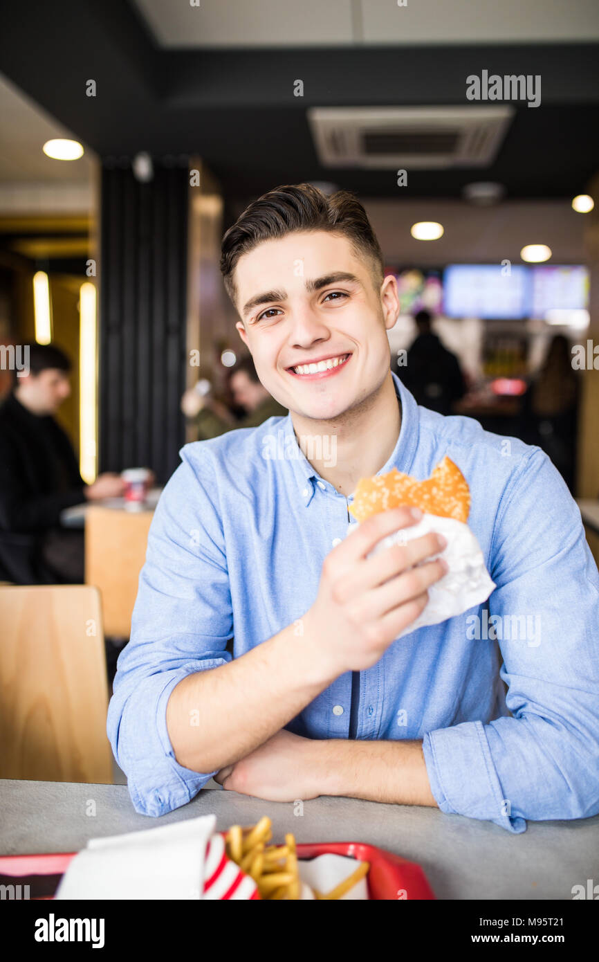 Man is eating in a restaurant and enjoying delicious food - Stock Image