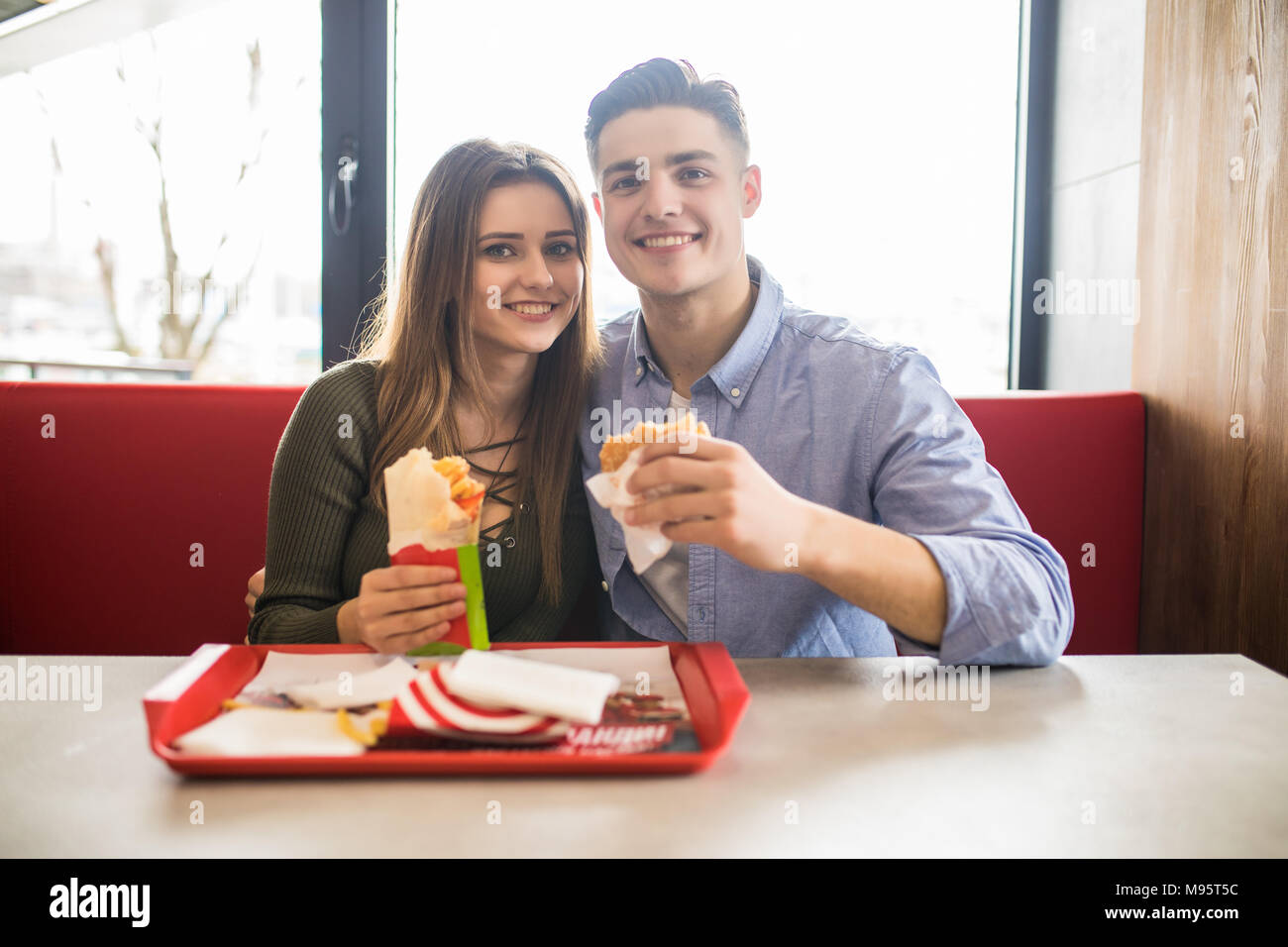 Happy couple eating fast food burger and doner in fast food cafe - Stock Image