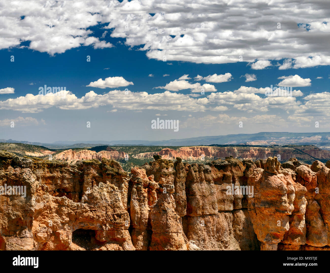 View of orange sandstone rock formations, cliffs snd steep hillsides under blue sky with white fluffy clouds. - Stock Image