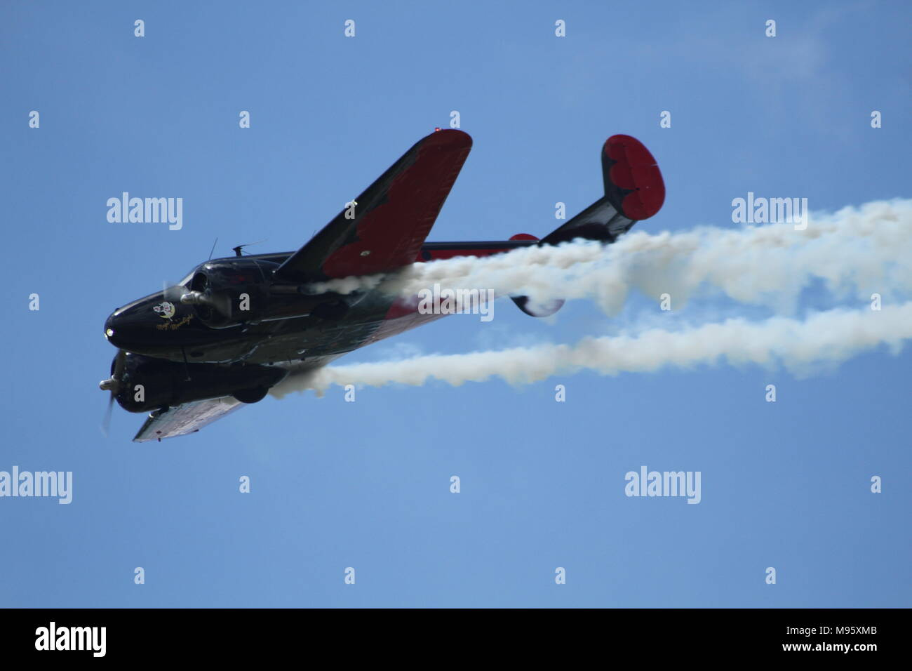 Beechcraft Model 18 performing an aerobatic show at an airshow - Stock Image