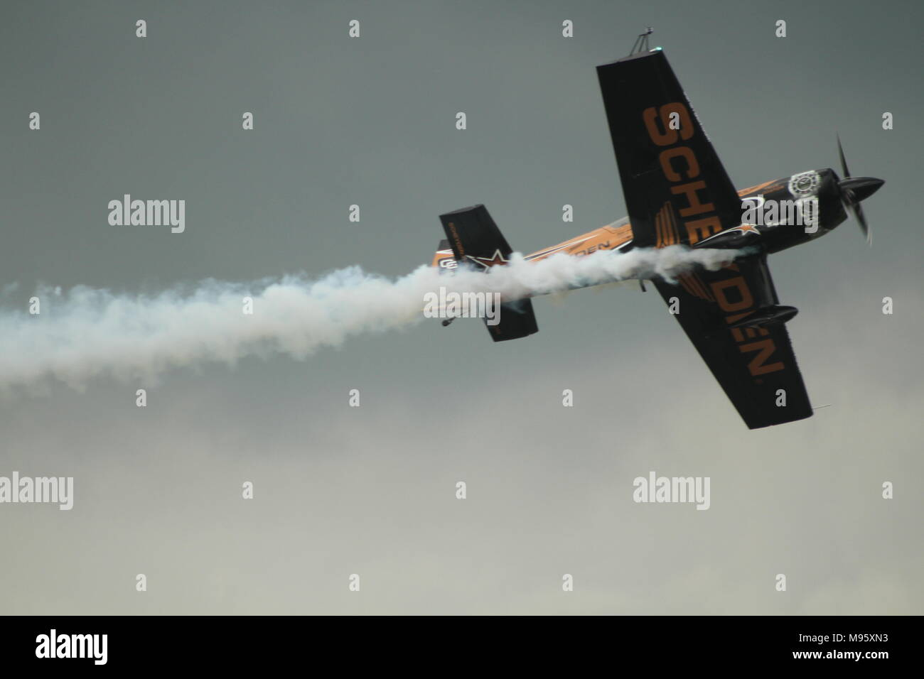 Aerobatic Plane Smoking while low flying at an air show - Stock Image