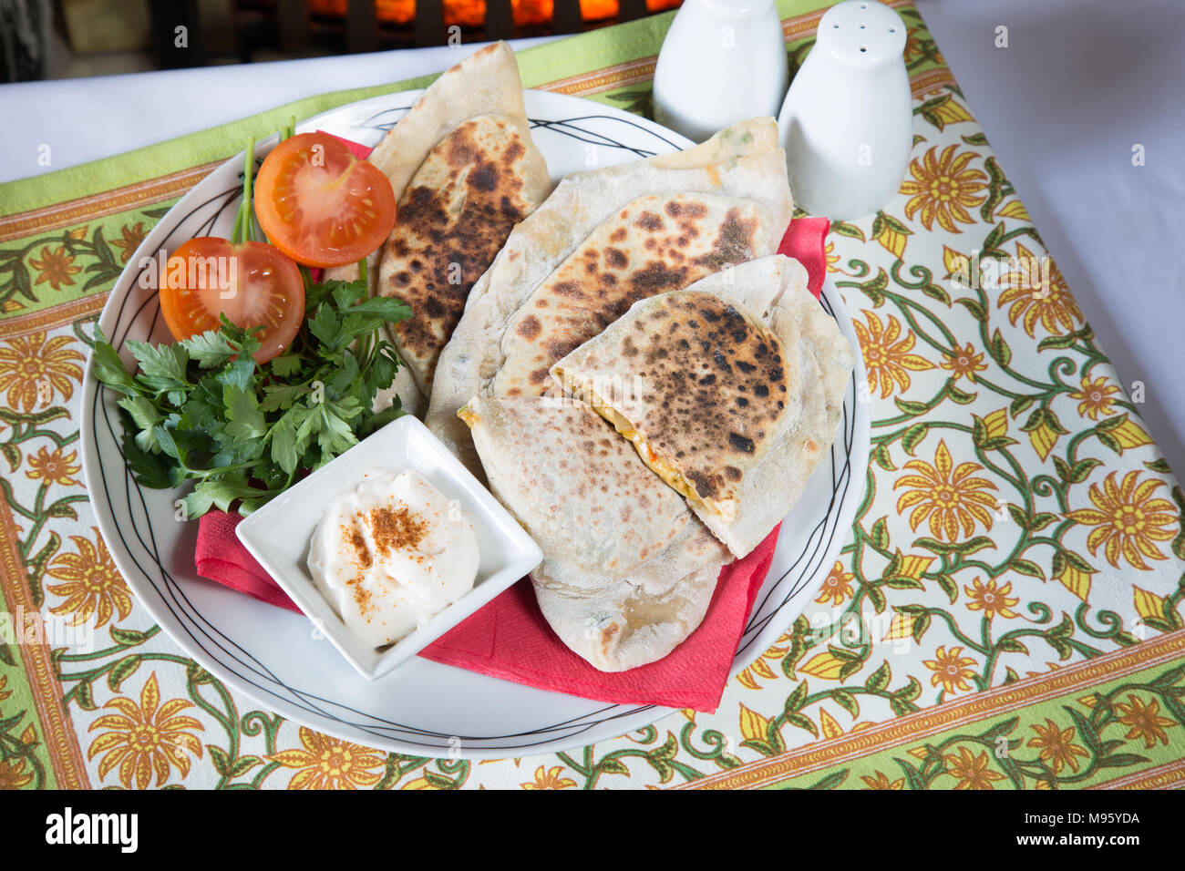Traditional Azerbaijani pie/Qutab with a cheese and herb filling served with a salad and sour cream with paprika dip - Stock Image