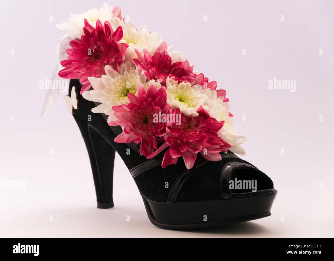 Flower arrangement in the women's high-heeled shoes. Unusual, unique and original boxes for flowers - Stock Image