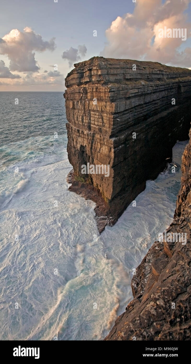 Waves crashing against cliffs at Loop Head on Ireland's Atlantic west coast in County Clare - Stock Image