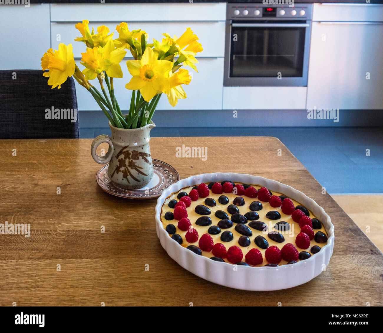 Kitchen scene - Daffodils in a pottery vase and delicious cheesecake In white dish with grape & berry topping on wooden table - Stock Image
