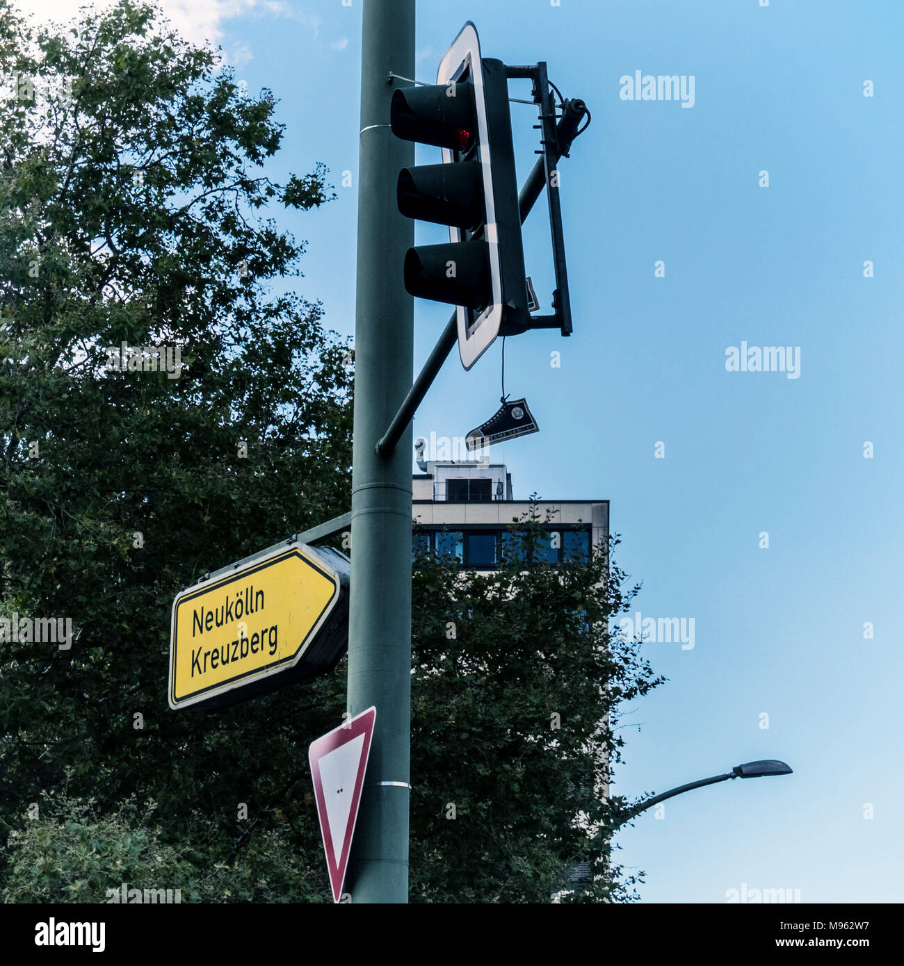 Yield sign, Street signs,traffic lights and suxpended shoe against blue sky, Berlin - Stock Image