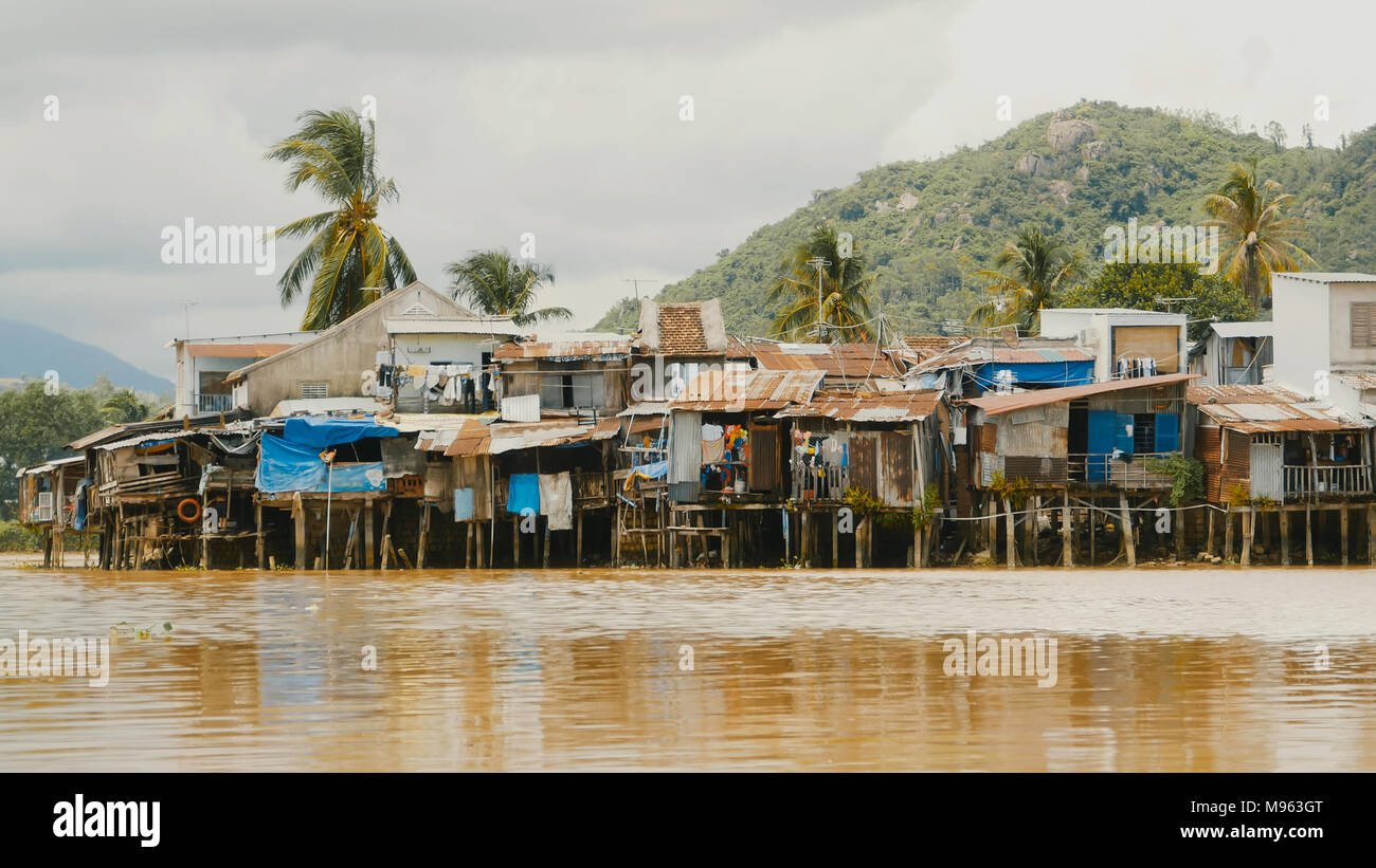 Slums in Nha Trang. Houses on the river. Vietnam. - Stock Image