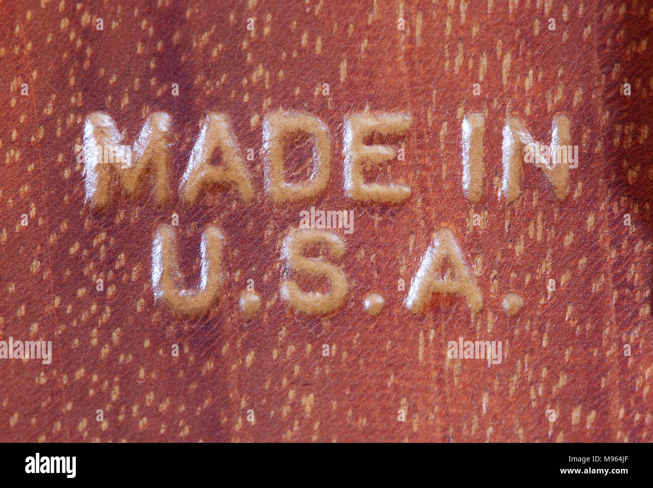 Made in U.S.A. routed into mahogany wood. - Stock Image