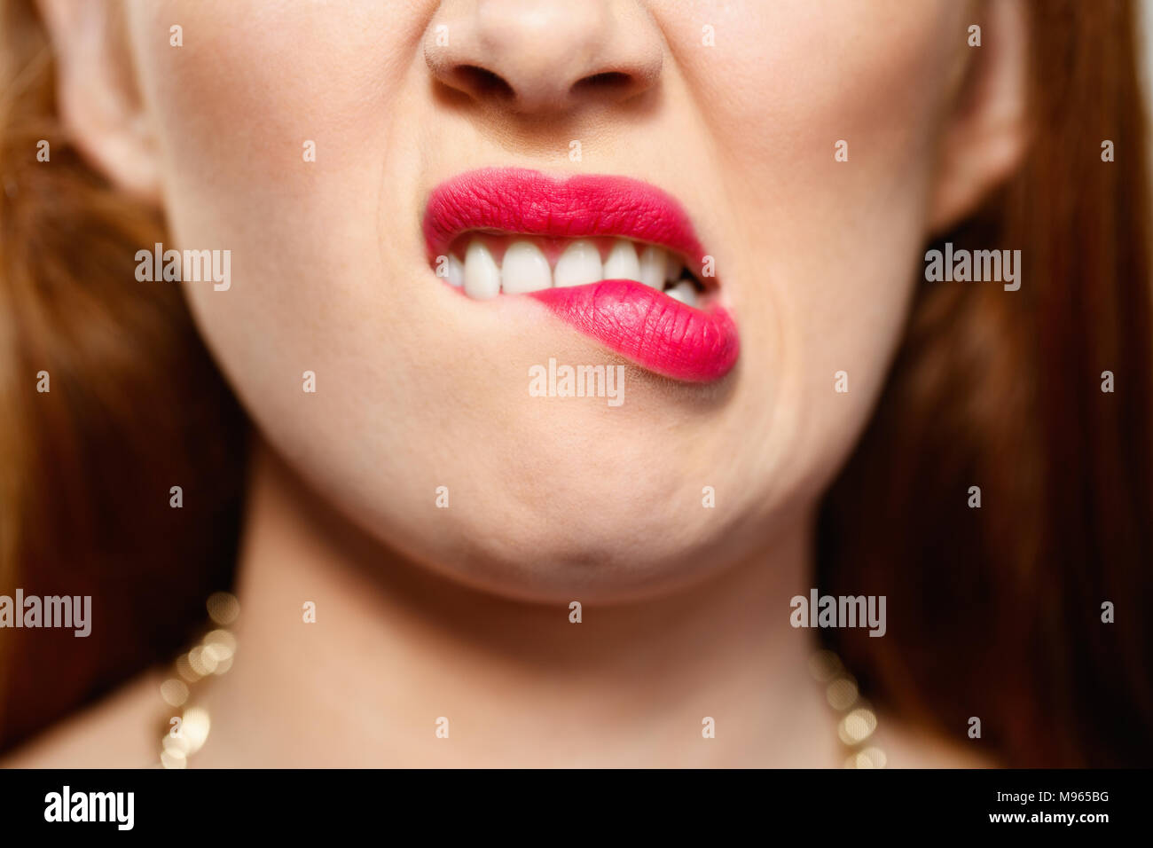 Portrait of insecure woman having doubts. Dubious redhead girl thinking, biting lips. Close up of mouth - Stock Image