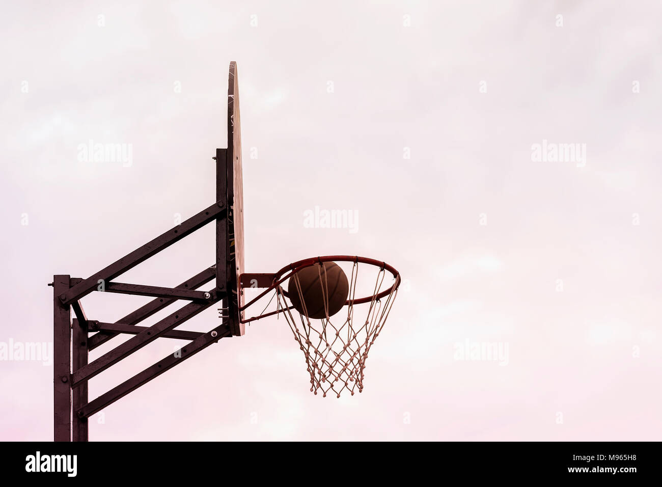 Basketball shield, ball going through basket on background of sky. Concept of sport, hit accuracy, active lifestyle. Copy space - Stock Image