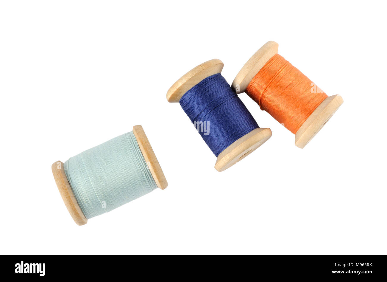 A wooden reels of thread on white background - Stock Image