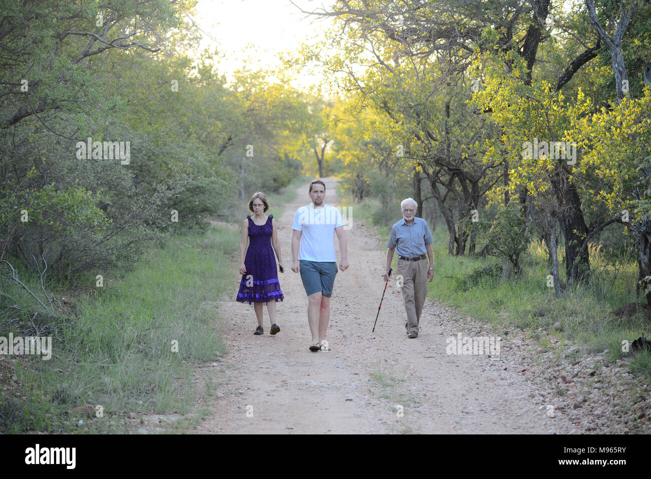 South Africa is a popular tourist destination for its blend of true African and European experiences. Family of three walking in nature reserve. - Stock Image