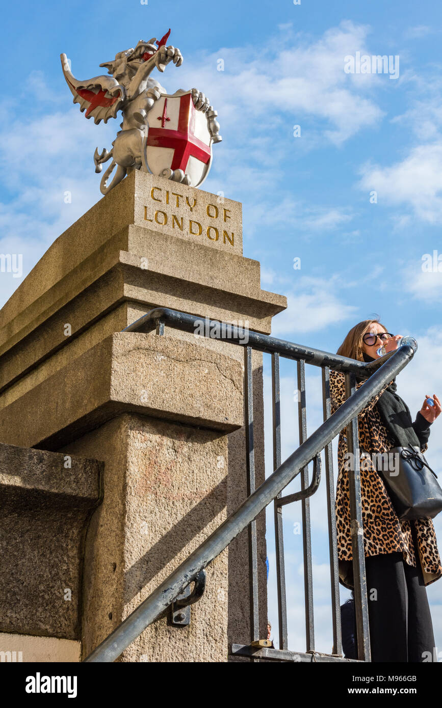 a young woman or lady female wearing a leopard print coat dinking from a bottle of water at the entrance to the city of London on London bridge. mood. - Stock Image