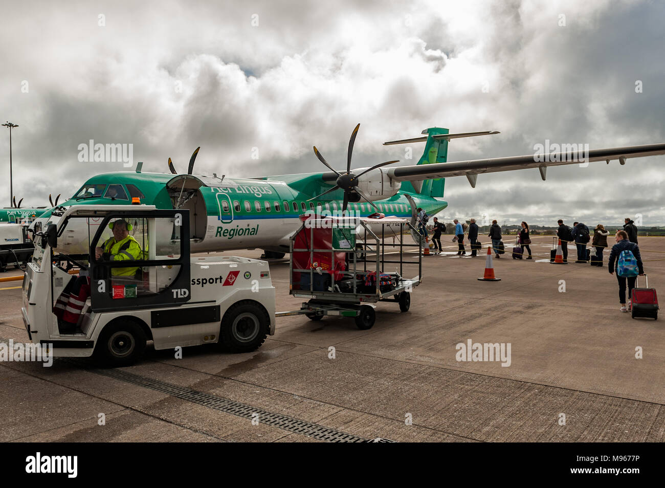 Passengers board an ATR 72-600 aircraft from Cork to Birmingham as a baggage handler drives a cart with baggage to be loaded into the hold. - Stock Image