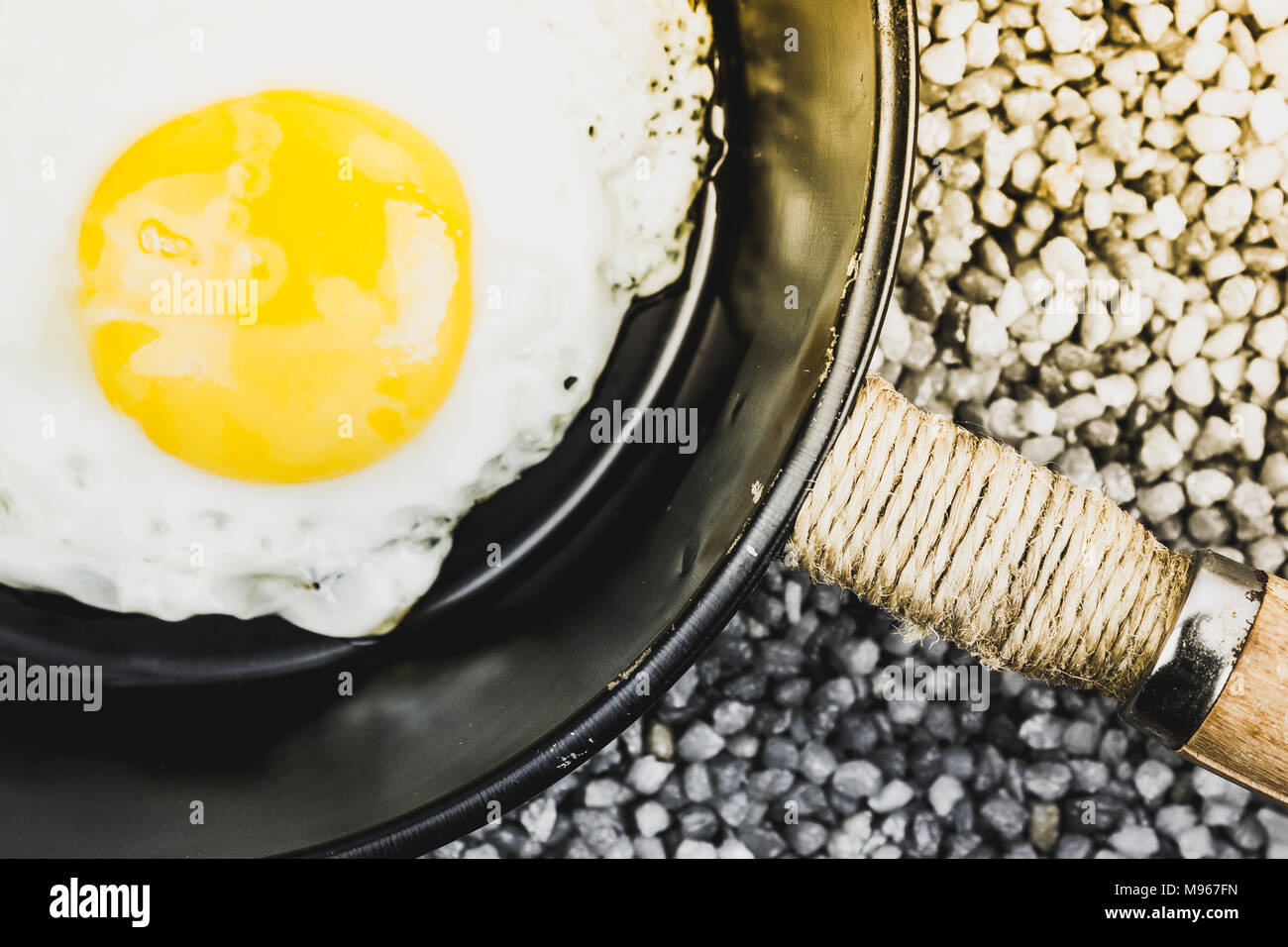 Fried egg in a frying pan on the gray gravel. Cooking dinner at home. Stock Photo