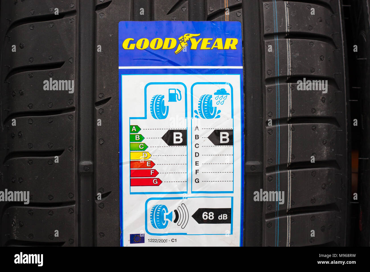 Brand new Goodyear car tyre with label with information about safety, fuel efficiency and external tyre noise. Editorial use only - Stock Image