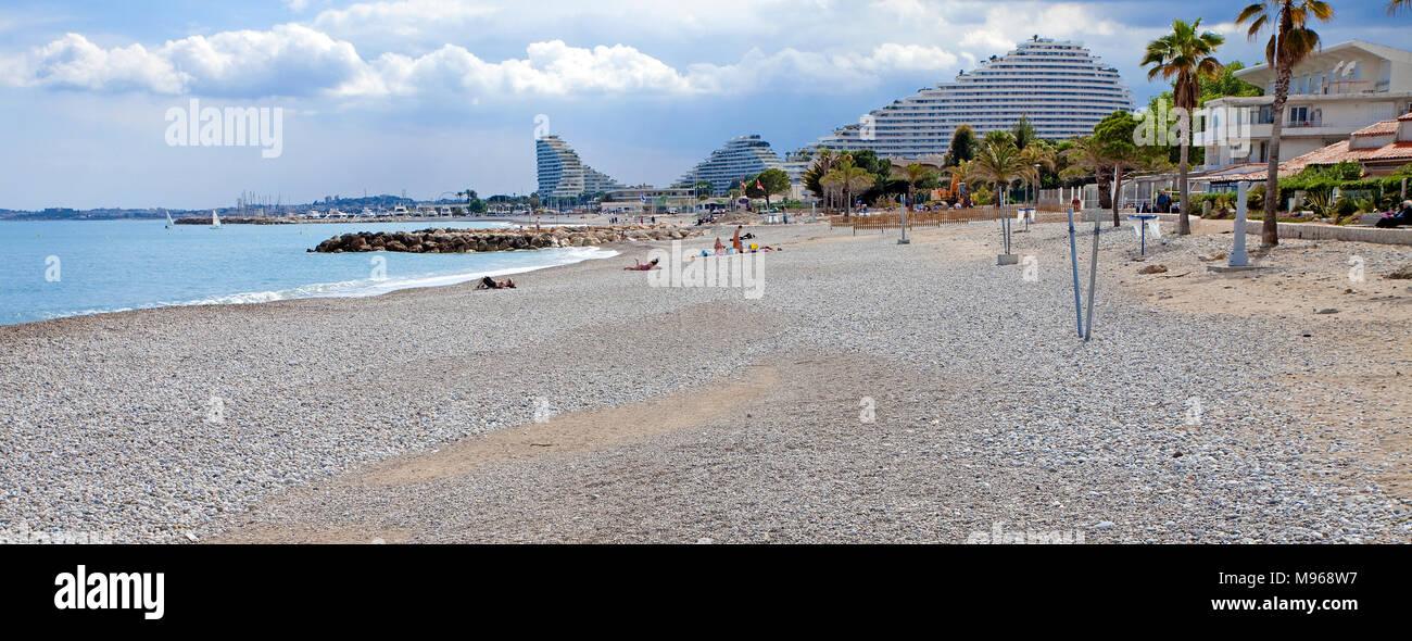 Pebble beach at Marina Baie des Anges, behind futuristic curved buildings of Villeneuve-Loubet-Plage, South France, Var, Cote Azur, France, Europe Stock Photo