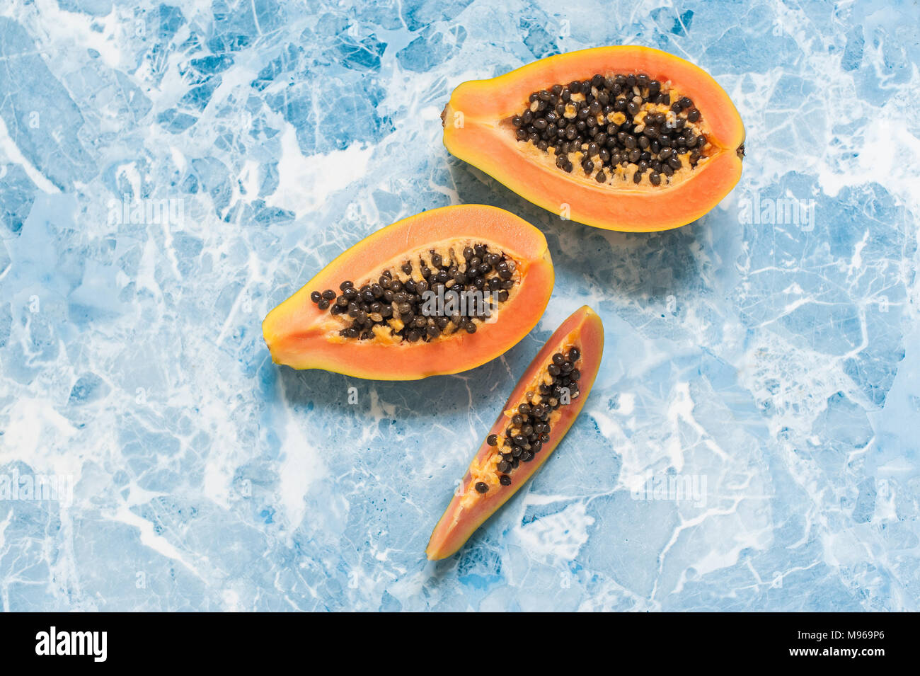 Juicy slices of ripe papaya on a blue background. Exotic fruits, healthy food. - Stock Image