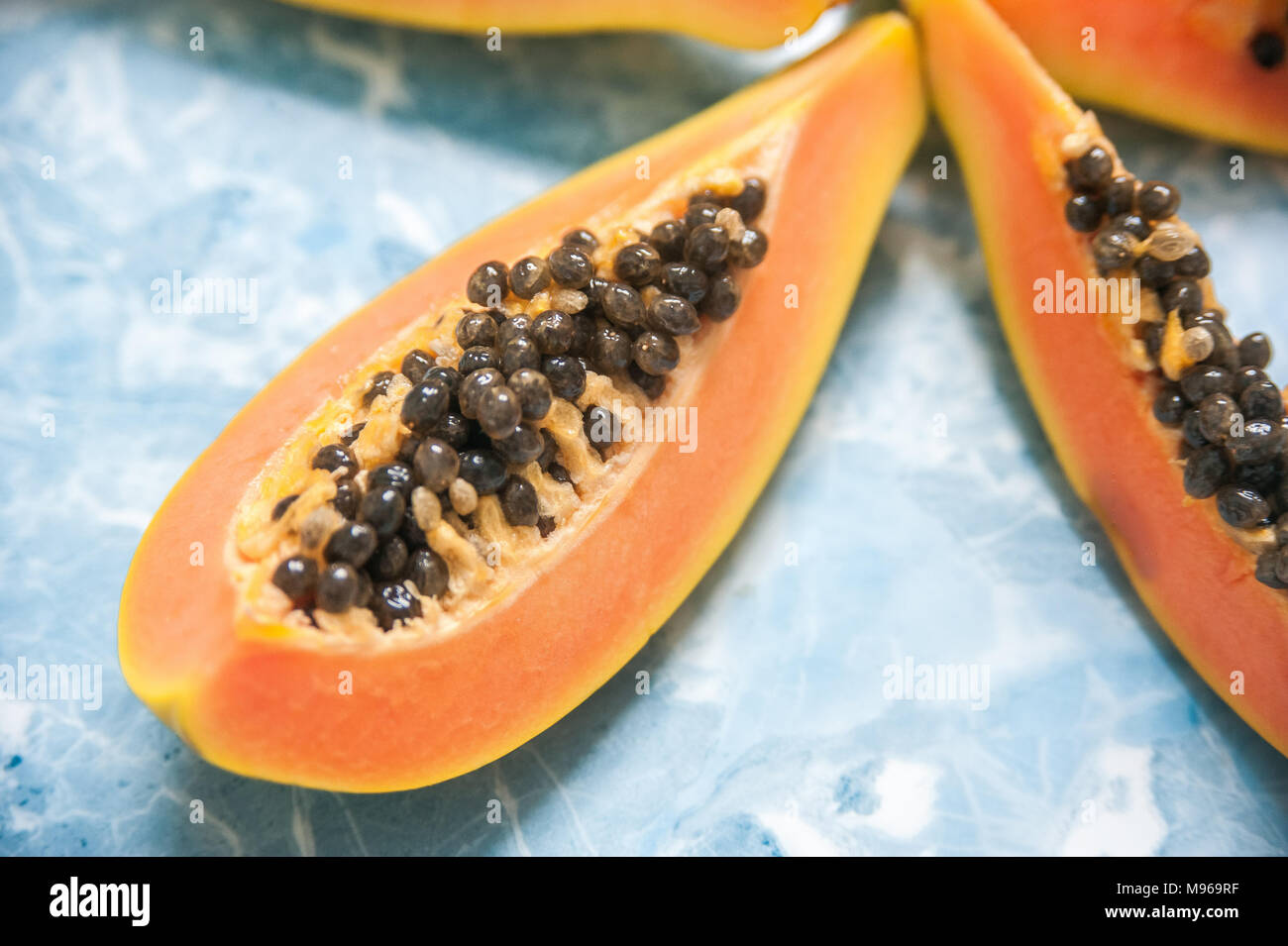 Juicy slices of ripe papaya on a blue background. Exotic fruits, healthy food. Stock Photo