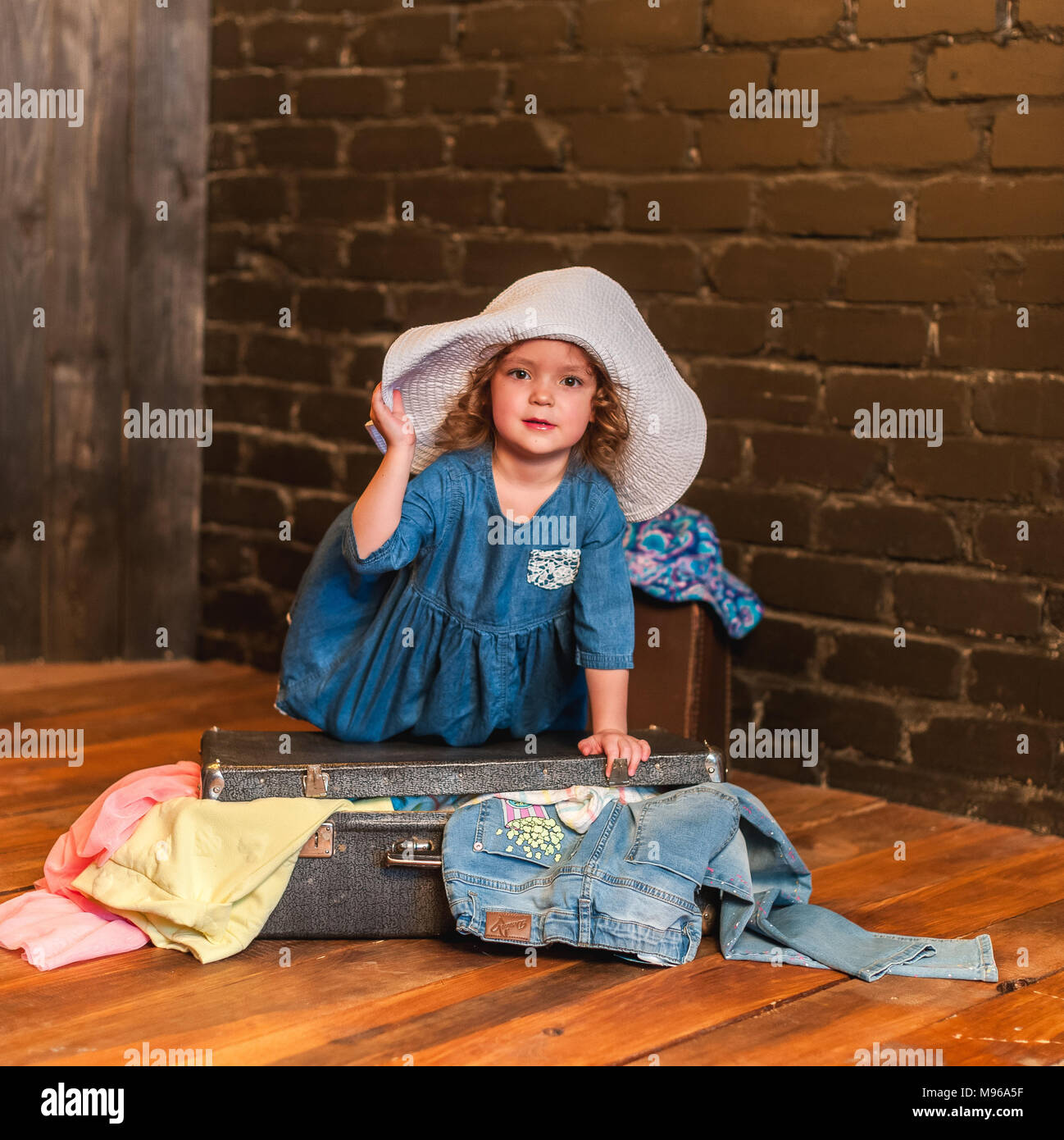 Little girl in a blue dress and white hat closes the suitcase with things. Little traveler preparing for a trip to Europe and Asia - Stock Image
