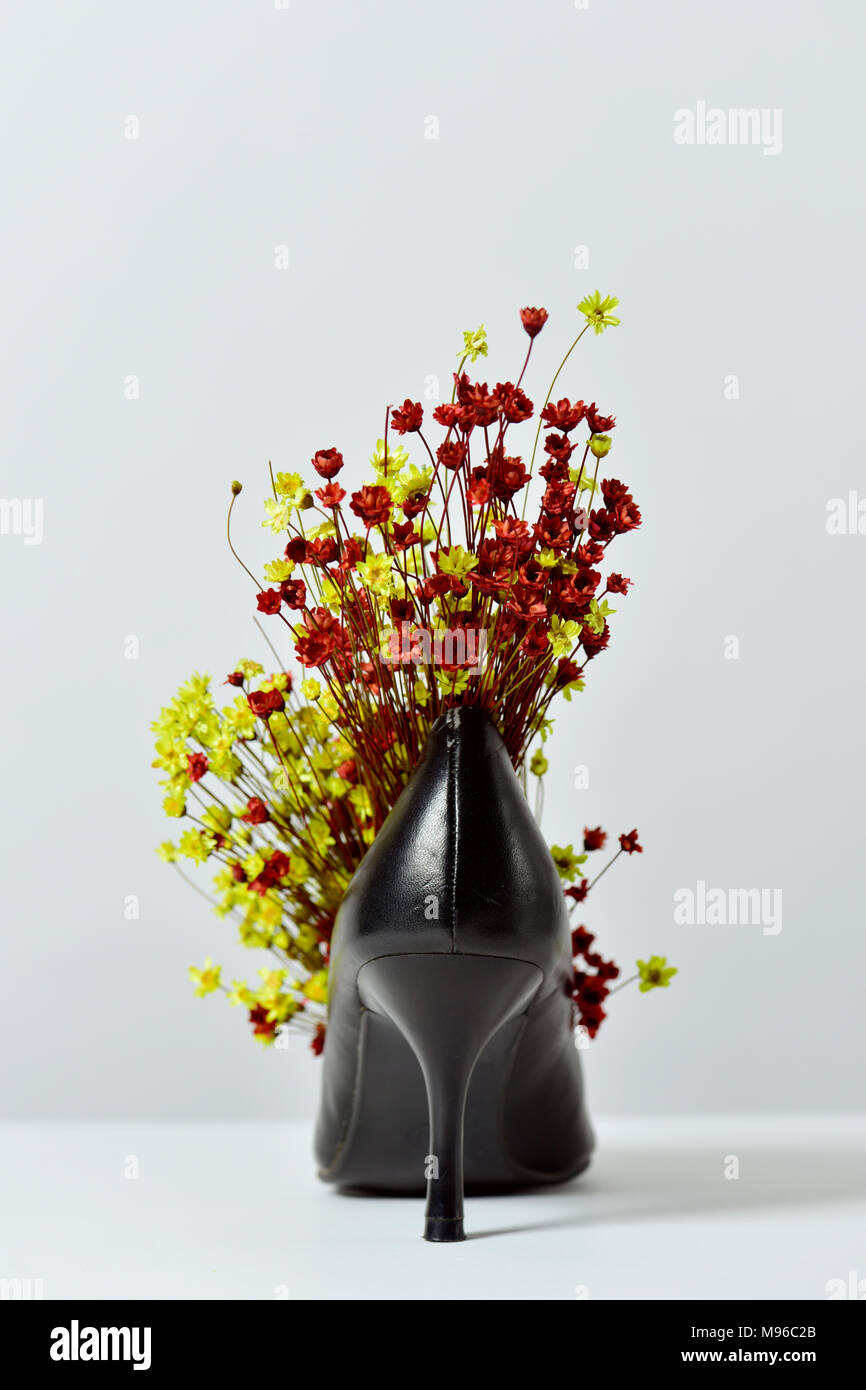 A Bunch Of Small Red And Yellow Flowers In A Black Leather High