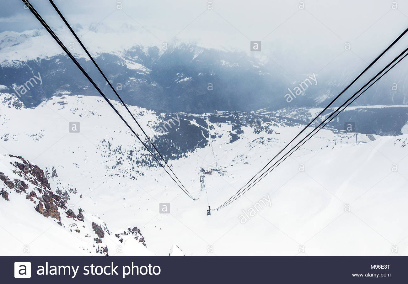 7th February 2016 - Courchevel 1850, France. Cable car lifting people on the top of the mountain. Ski resort landscape panorama. - Stock Image