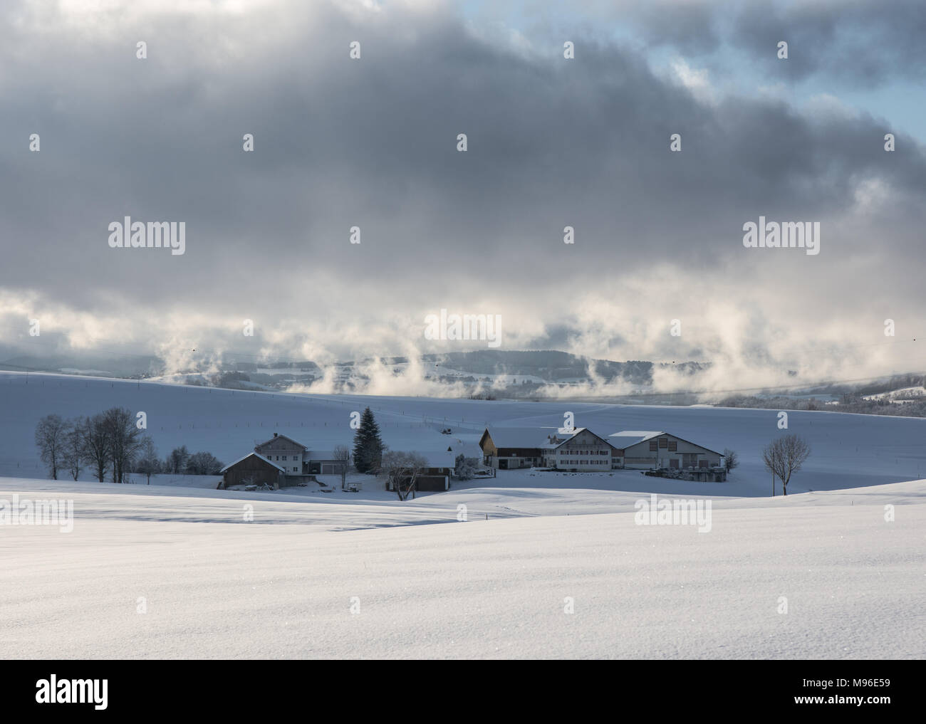 low hanging clouds over farmhouses in wintry Allgäu Stock Photo
