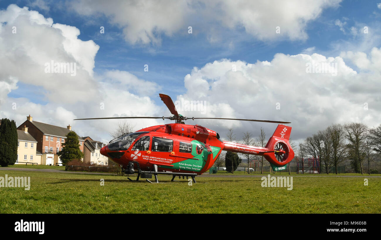 Wide angle view of an Airbus helicopter of the Wales Air Ambulance service on the ground in a housing estate on an emergency mission - Stock Image
