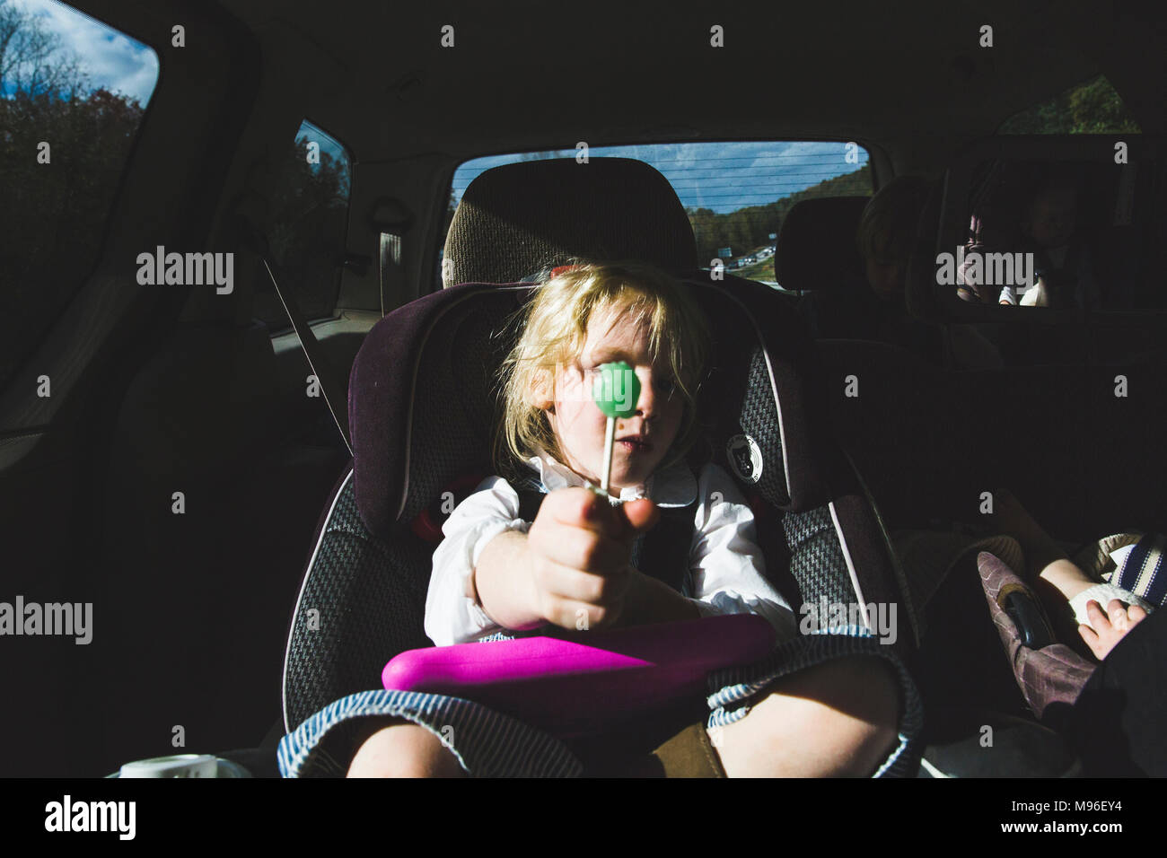 Girl with green lollipop sitting in car seat - Stock Image
