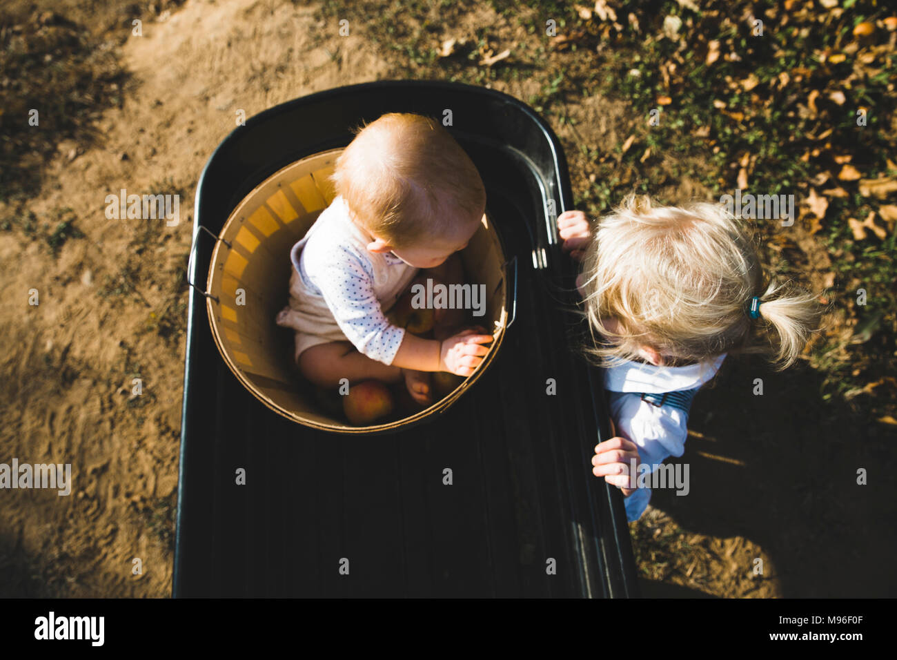 Girl and baby together in orchard baskets - Stock Image
