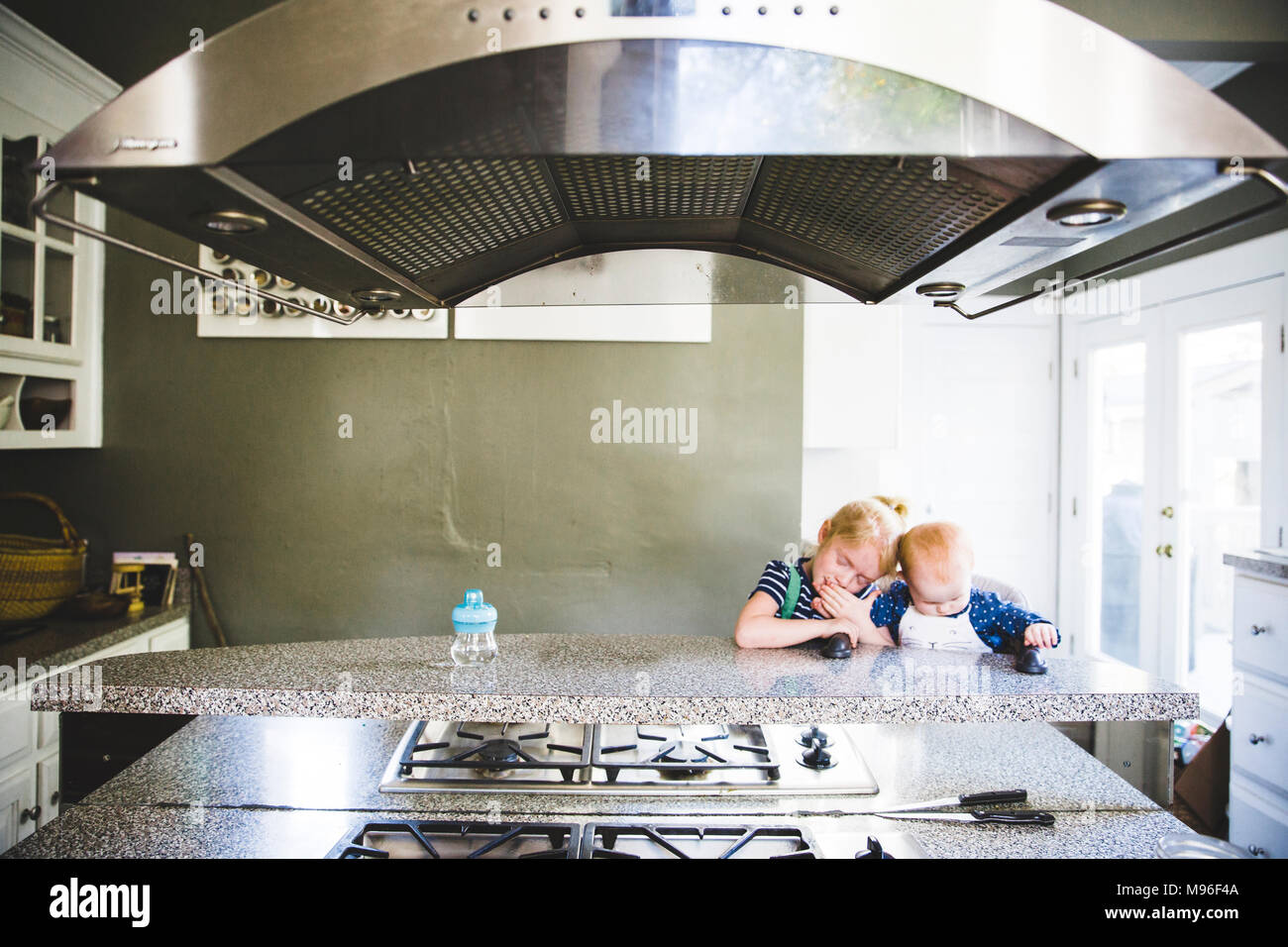 Girl and baby sitting at kitchen counter - Stock Image
