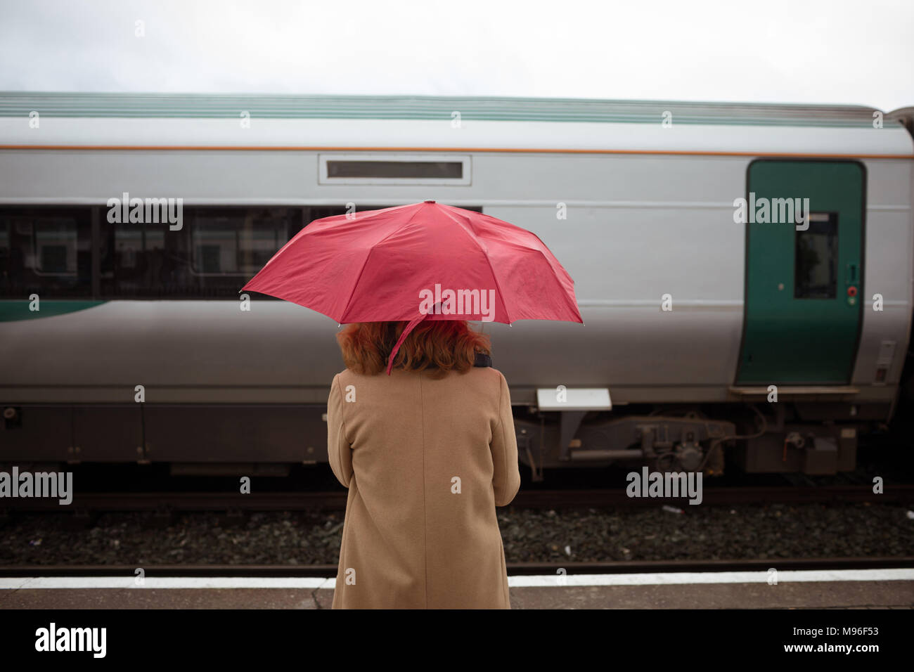 Beautiful young woman with umbrella waiting for train on platform - Stock Image
